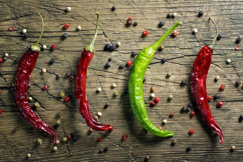 4558830-red-and-green-chili-peppers-and-pepper-mix-on-vintage-wooden-table-background